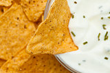 Close up of a nacho dipped into a bowl of dip