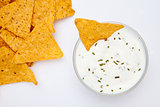 Bowl of dip with herbs with a nacho dipped in it