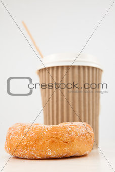 A doughnut and a cup of coffee placed side by side