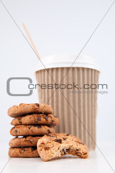 Five cookies and an half eaten cookie and a cup of coffee placed