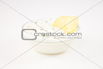 Bowl of dip with herbs with a chip dipped in it