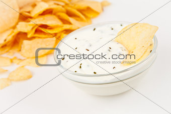 Bowl of  dip with herbs beside chips