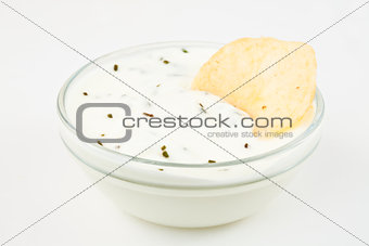 Bowl of white dip with herbs and a nacho dipped in it