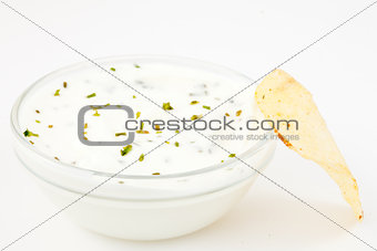 Bowl of white dip with herbs and a chips