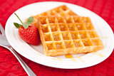 Waffles and strawberry together in a white plate