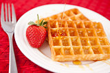Waffles and syrup and strawberry together in a white plate