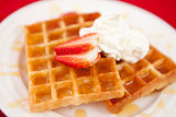 Waffles with whipped cream and strawberry and syrup