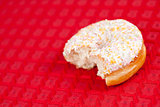 Half doughnut on a red tablecloth