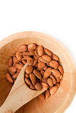Wooden spoon with almonds in a bowl