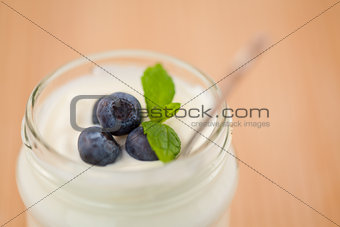 Close up of a pot of yoghurt with leaves and blueberries