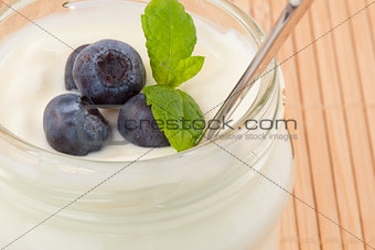Close up of four blueberries in a pot of yoghurt