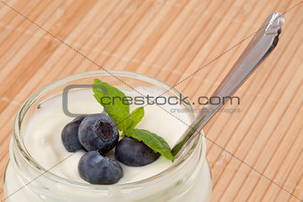 Close up of four blueberries in a yogurt