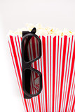 Glasses hanging on a box full of popcorn
