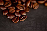 Dark blurred coffee seeds laid out together on a black table