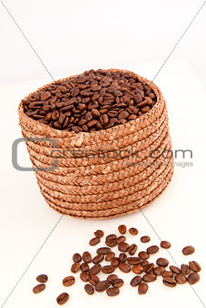 Close up of a basket full of coffee seeds with seeds lying in fr