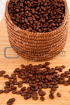 Close up of a basket filled with coffee seeds on a wooden tablec