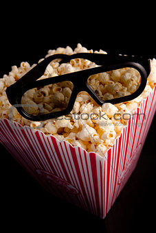 3D glasses lying on the top of a box of popcorn