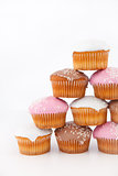 Many muffins with icing sugar placed in pyramid