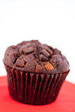 Dark chocolate muffin on a red table