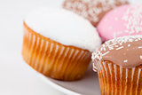 Close up of muffins with icing sugar on a white plate