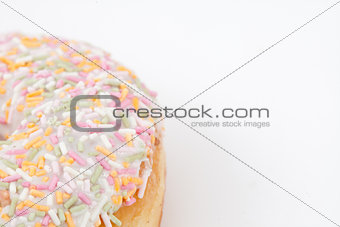 Close up of a doughnut with multi coloured icing sugar