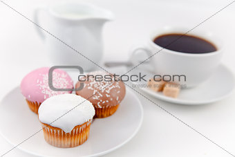 Small muffins and coffee on white plate with sugar and milk