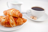 Two croissants and a cup of coffee on white plates with sugar an