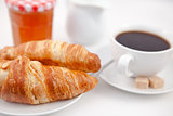 Croissants and a cup of coffee on white plates with sugar milk a