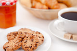 Cookies and a cup of coffee on white plates with sugar croissant