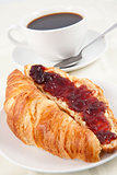 Coffee cup behind a croissant