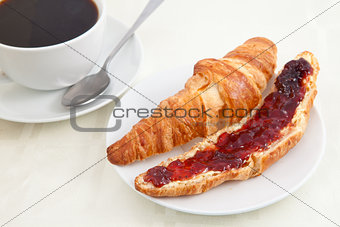 Croissant next to a coffee cup