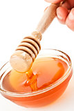 Honey dipper on the top of a bowl dropping honey