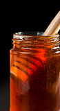 Close up of a honey jar with a honey dipper