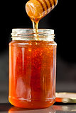 Honey sticky trickle dropping in a jar