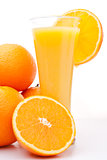 Pile of oranges near a glass of orange juice