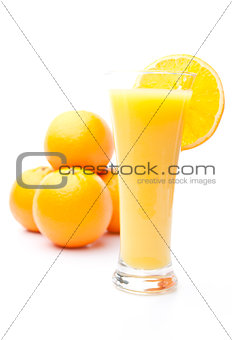 Pile of oranges behind a glass of orange juice