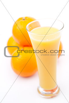 Oranges behind a glass of orange juice