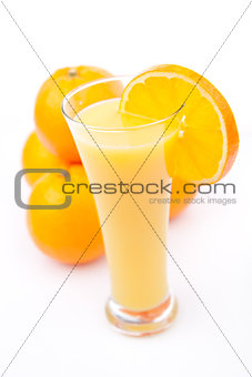Full glass of orange juice placed near a heap of oranges