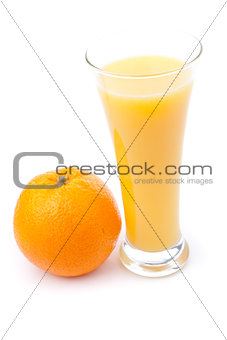 Glass full of orange juice placed near an orange