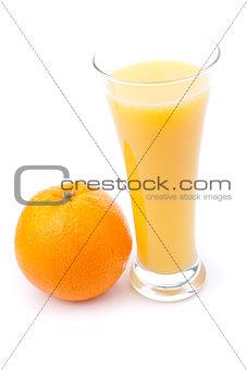 Glass full of orange juice placed near an orange