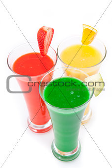 Three glasses full of fruit juice with fruits pieces