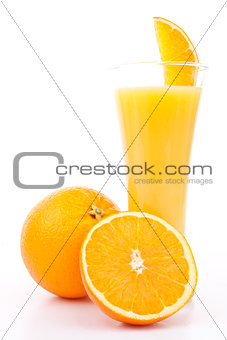 One orange and a half next to a glass of orange juice