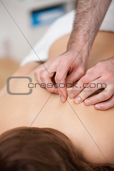 Back of a woman being massaging while fingertips of doctor