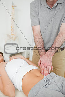 Doctor examining the painful abdomen of a woman