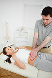 Serious osteopath palpating the stomach of a patient