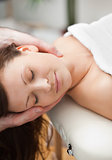 Peaceful woman being massaging on the neck by a therapist