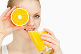 Woman placing an orange on her eye while drinking