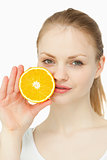 Woman placing an orange on her lips
