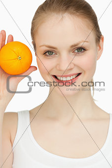 Smiling blonde-haired presenting an orange