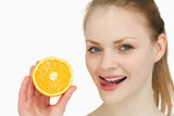 Woman holding an orange while placing her tongue on her lips